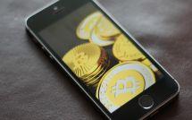 Монеты Биткоина на дисплее смартфона